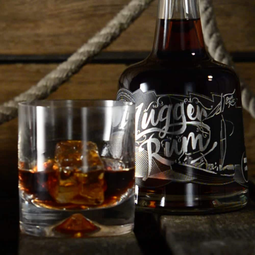 Glass filled with Lugger Rum with bottle in the background
