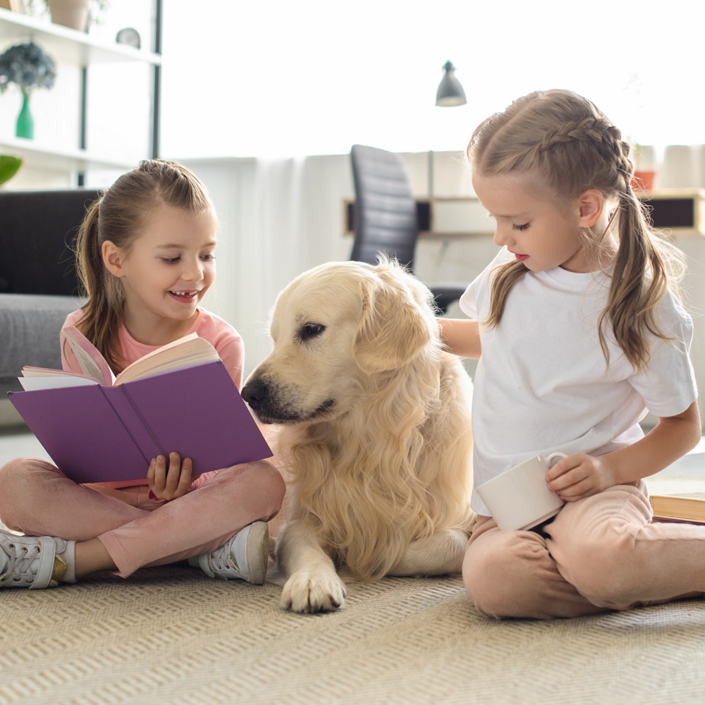 Children reading book to a dog